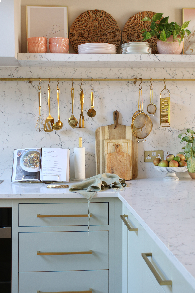 marble kitchen worktop with gold utensil hanging rails