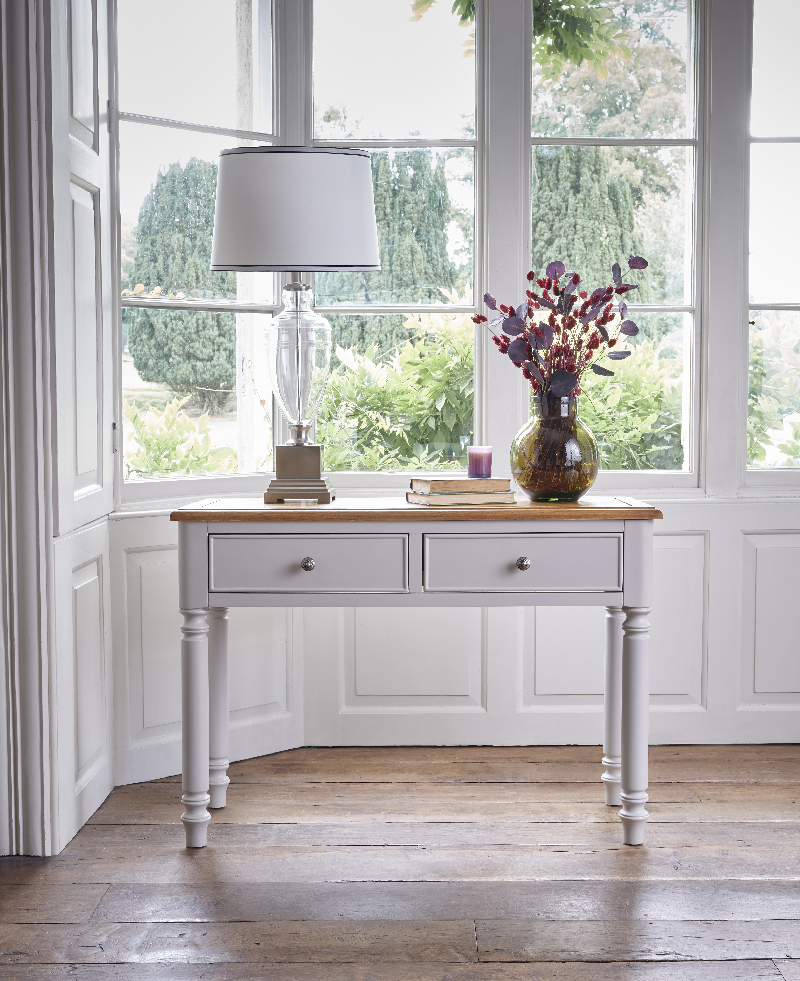 grey green painted console table with a lamp and flowers