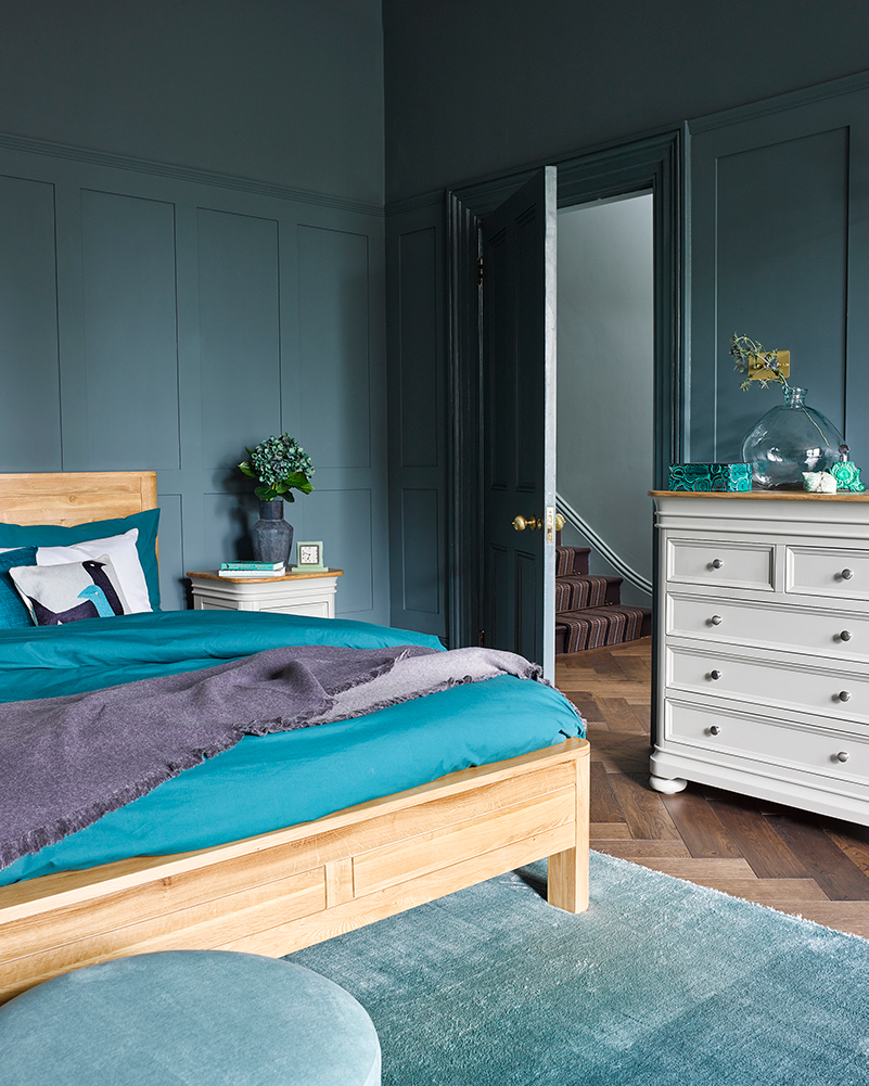 blue green toned bedroom with oak double bed