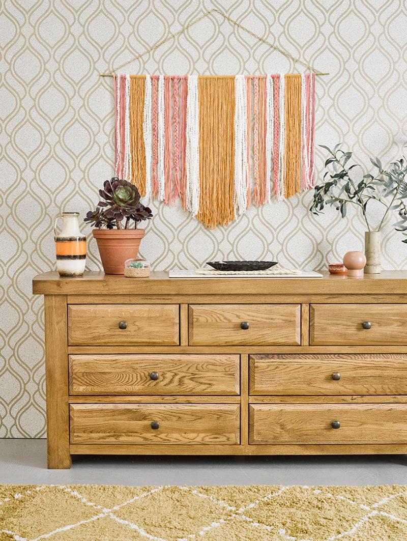 light oak chest of drawers against geometric wallpaper