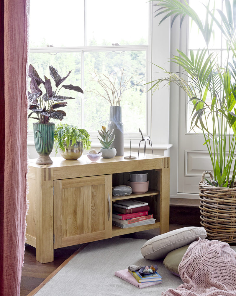 oak tv stand in bay window topped with floral accessories