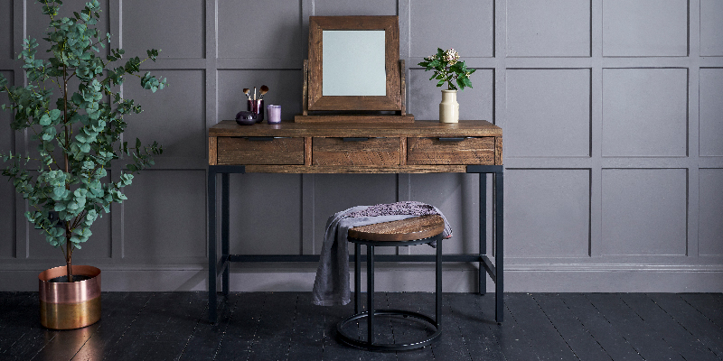 dark wood dressing table against blue panelled wall