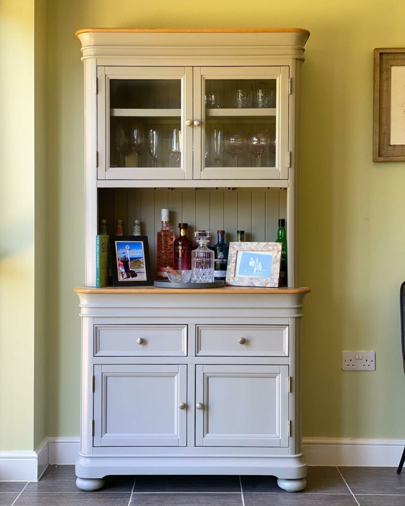 Grey painted dresser against yellow wall