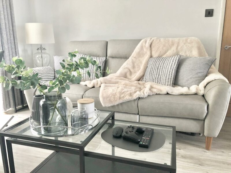 Grey leather sofa with throw and cushions