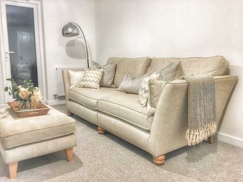 Beige sofa and footstool with grey cushions and throws