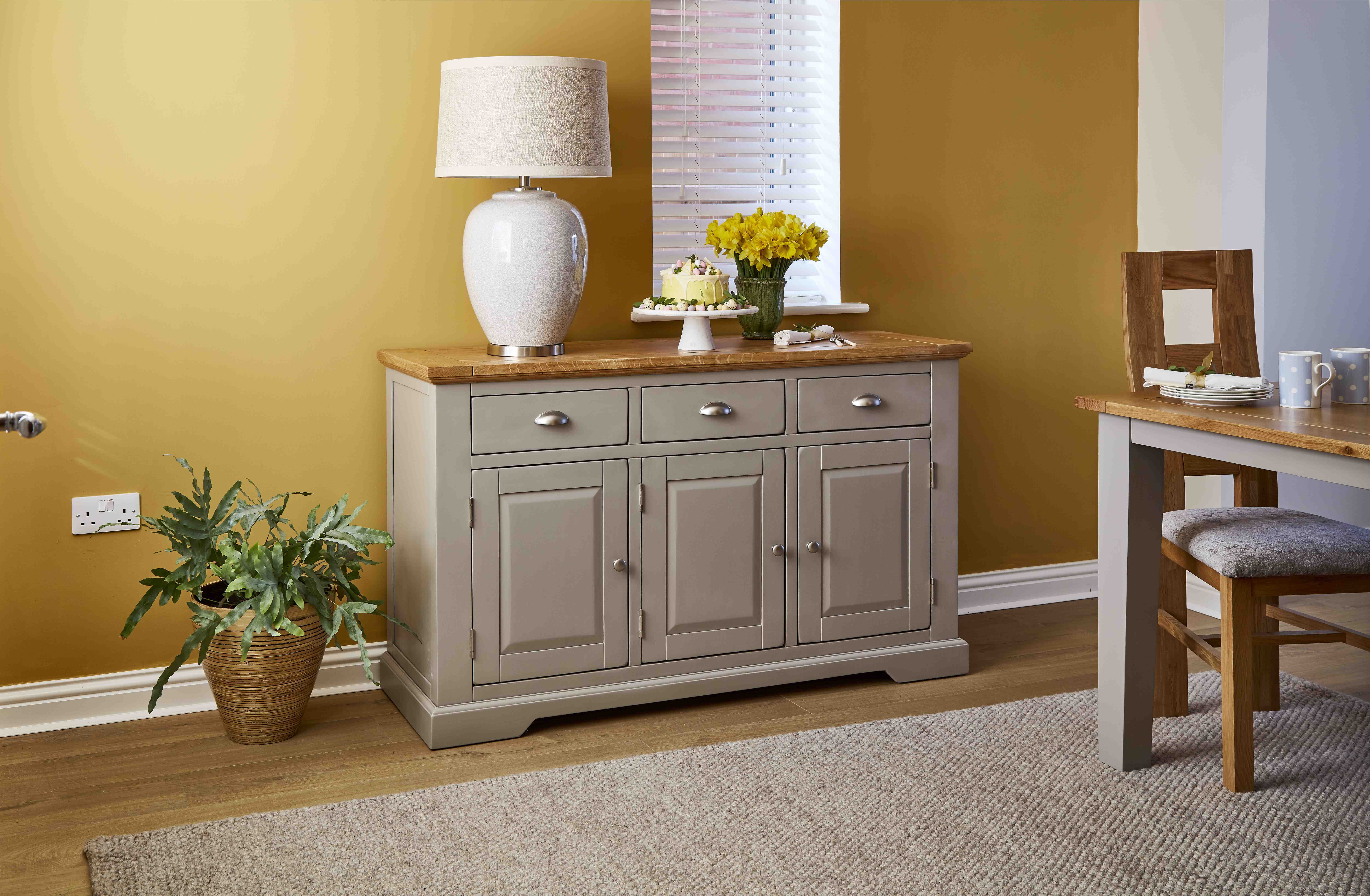 Grey sideboard against yellow living room wall