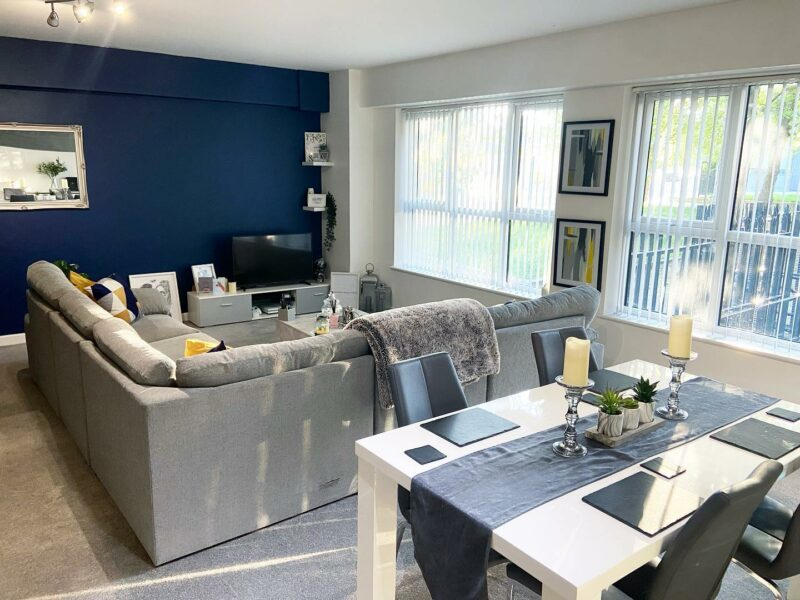 Living and dining space with table and grey sofa
