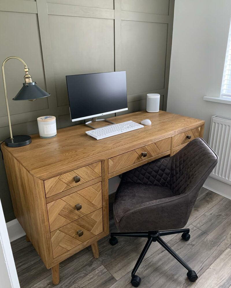 Parquet desk in home office with green wall