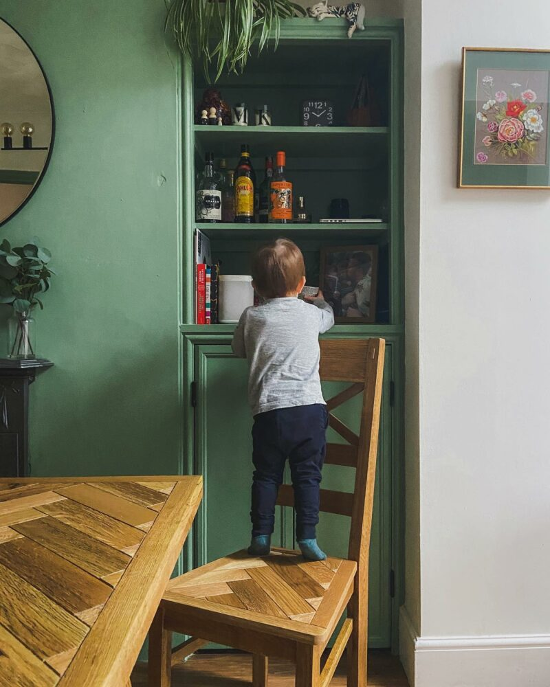 Parquet dining set in green kitchen with open shelving