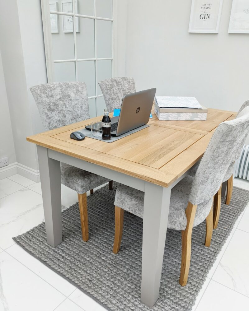 Home working from wooden dining table with grey fabric chairs